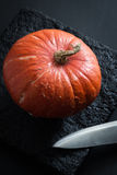Ripe Pumpkin and a Sharp Blade on a Black Stone Plate Stock Photo