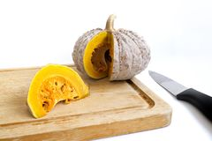 Ripe pumpkins cut into pieces. On wooden block Stock Photo