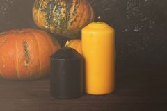 Ripe pumpkins, orange and black candle on a green background. To Stock Photos