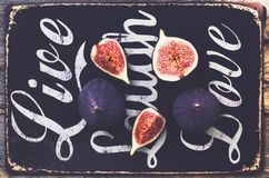 Ripe purple fig slices on wooden background Stock Photo