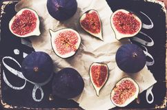 Ripe purple figs on black background. With letters Stock Photos