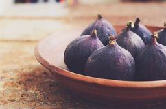 Ripe purple figs in clay bowl with empty space on rusty background Stock Photos