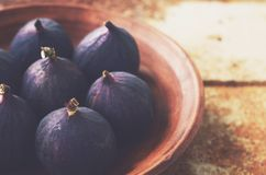 Ripe figs in clay bowl on grunge metal background Royalty Free Stock Photography