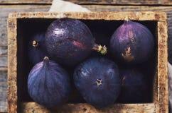 Ripe purple figs in rusted wooden box Stock Photo