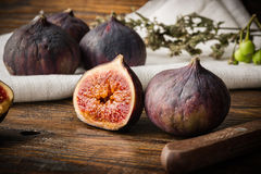 Ripe, purple figs on wooden table with sliced one Royalty Free Stock Images