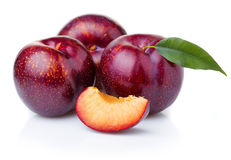 Ripe purple plum fruits with green leaves isolated on white. Background stock photos