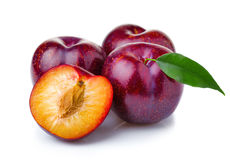 Ripe purple plum fruits with green leaves isolated on white Royalty Free Stock Photo