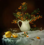 Ripe quince and mountain ash branch in a jug. Still-life with a yellow quince and a mountain ash branch in a white ceramic jug royalty free stock photo
