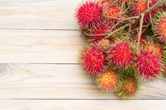 Ripe rambutan on wooden background. Rambutan  on wooden background , Top view Royalty Free Stock Images
