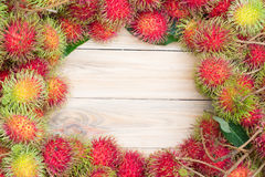 Ripe rambutan on wooden background. Rambutan  on wooden background , Top view Stock Image