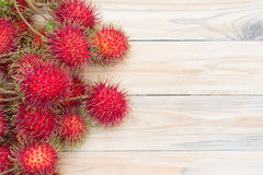 Ripe rambutan on wooden background. Rambutan  on wooden background , Top view Stock Photos