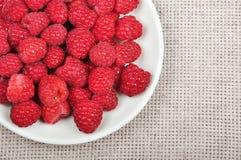 Ripe raspberries. Crockery with beautiful ripe raspberries on light tablecloth Stock Photo