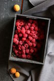 Ripe raspberries and apricots on the table Royalty Free Stock Photo