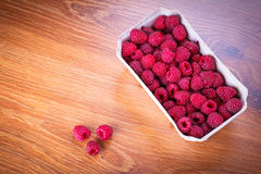 Ripe raspberries in the basket. On wooden board Royalty Free Stock Photos