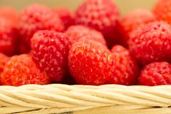 Ripe raspberries in the basket on wooden. Closeup Stock Photo