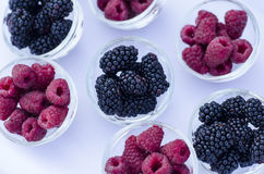 Ripe raspberries with blackberries in a glass cup Royalty Free Stock Images