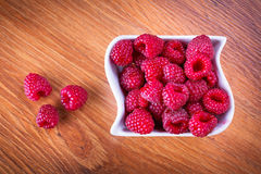 Ripe raspberries in the bowl. On wooden board Stock Photo