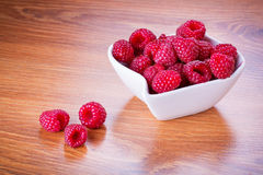 Ripe raspberries in the bowl. On wooden board Royalty Free Stock Photography