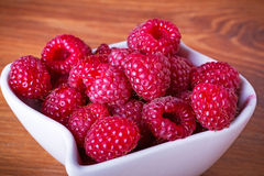 Ripe raspberries in the bowl. On wooden board Stock Photography