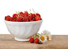Ripe raspberries in a bowl on a wooden table on a white backgrou Royalty Free Stock Photo
