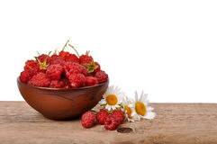 Ripe raspberries in a bowl on a wooden table on a white backgrou Stock Photos