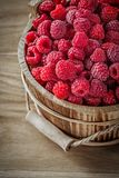 Ripe raspberries in bucket on wooden board.  Royalty Free Stock Photography