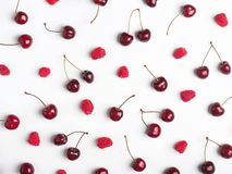 Ripe raspberries and cherries on the white background. Creative food pattern Stock Images