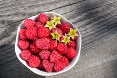 Ripe raspberries in a Cup. Raspberries in a Cup on wooden surface the view from the top Royalty Free Stock Image