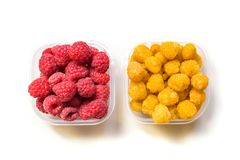 Ripe raspberries in glass bowl isolated on white. Ripe yellow and red raspberries in glass bowl isolated on white background Stock Images