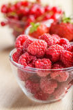 Ripe raspberries. In glass plate on wooden table Stock Photo