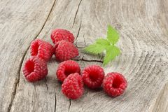 Ripe raspberries with green leaf on old wooden table Royalty Free Stock Images