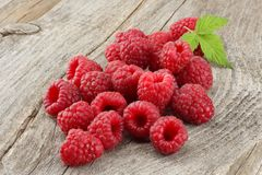 Ripe raspberries with green leaf on old wooden table Stock Photos