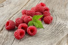 Ripe raspberries with green leaf on old wooden table Royalty Free Stock Image