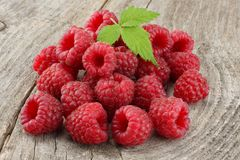 Ripe raspberries with green leaf on old wooden table Stock Photography