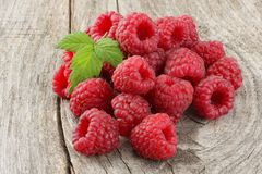 Ripe raspberries with green leaf on old wooden table Royalty Free Stock Photography