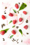 Ripe raspberries, mint leaves, jam and green tea on a white back Stock Photo