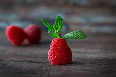 Ripe raspberries and mint on a wooden background Royalty Free Stock Photos