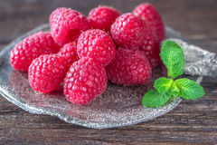 Ripe raspberries and mint on a wooden background Royalty Free Stock Image