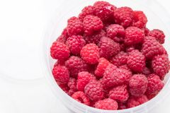 Ripe raspberries in a plastic bucket on a light background stock photography