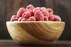Fresh raspberry in a wooden plate. Ripe raspberries on a plate, close up Stock Photos