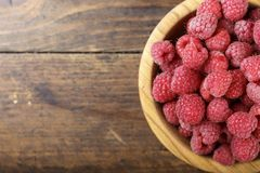 Fresh raspberry in a wooden plate. Ripe raspberries on a plate, close up Royalty Free Stock Photo