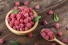 Fresh raspberry in a wooden plate. Ripe raspberries on a plate, close up Royalty Free Stock Photos