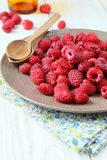 Ripe raspberries on a plate and spoon Royalty Free Stock Photography