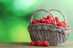 Ripe raspberries. In basket on wooden table Stock Images