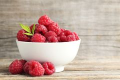 Ripe raspberries. In bowl on wooden table Stock Photo