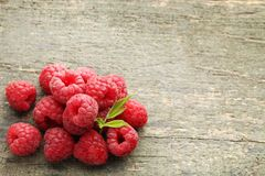 Ripe raspberries. With green leaf on wooden table Royalty Free Stock Photos