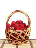Ripe raspberries. In a wicker basket on a straw mat over white background Stock Photo
