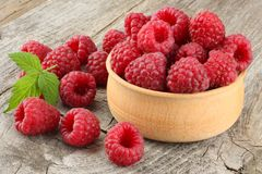Ripe raspberries in wooden bowl on old wooden table background Royalty Free Stock Photography
