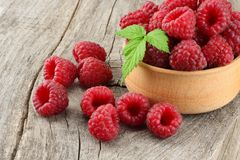 Ripe raspberries in wooden bowl on old wooden table background Stock Images