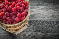 Ripe raspberry in bucket on vintage wooden board.  Stock Photography